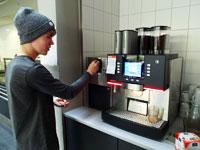 Zuerst wird das Geld in den Kaffeeautomaten eingeworfen.